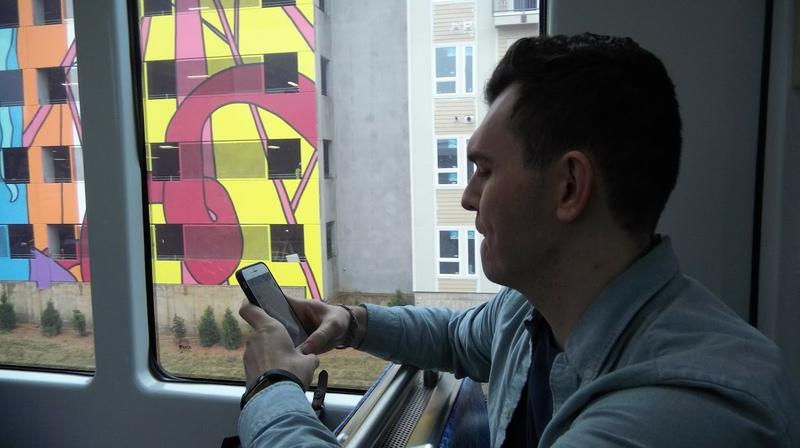 Michael Fleming takes a photo of his NoDa apartment building from the Blue Line light rail train during a test ride Tuesday.