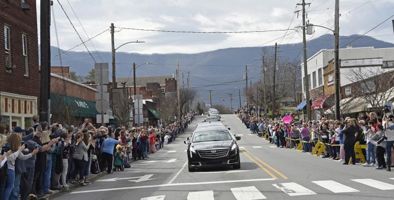 People line the street to pay respects as the hearse carrying the body of Rev. Billy Graham travels through Black Mountain, N.C., Saturday, Feb. 24, 2018.