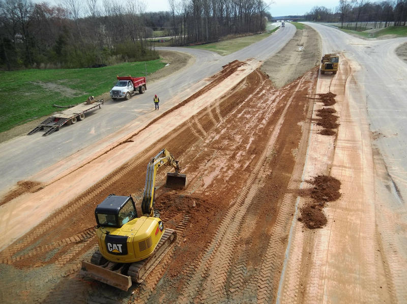 Workers are grading the median on the Monroe Expressway north of Monroe.