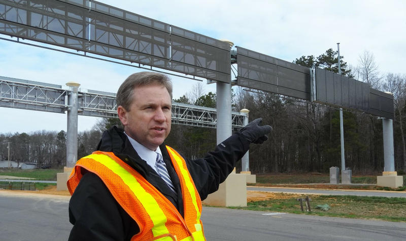 Dennis Jernigan of the N.C. Turnpike Authority points out a gantry on the Monroe Expressway for electronic toll equipment.