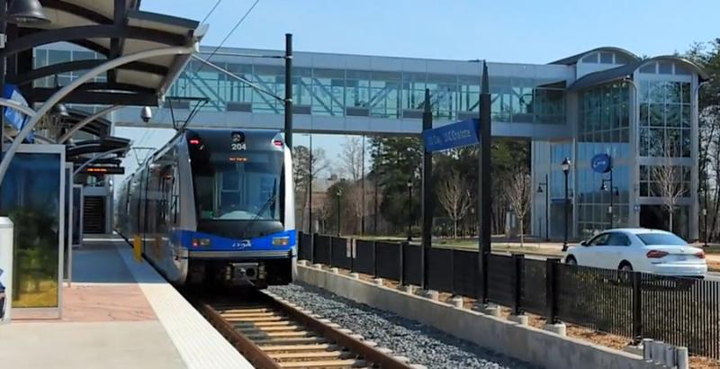 A Blue Line train pulls away from J.W. Clay Station on N. Tryon Street.