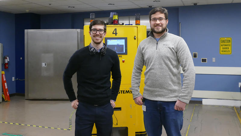 WFAE's Nick de la Canal (left) with Cailen Sniker pose with one of the Fed's automated guided vehicles, which man the underground vault.