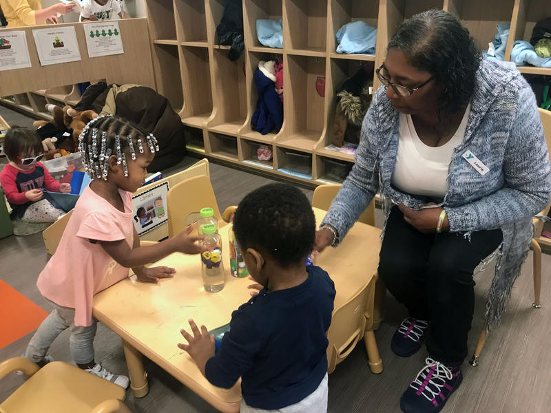 A teacher at the Howard Levine Child Development Center helps students make sound shakers.