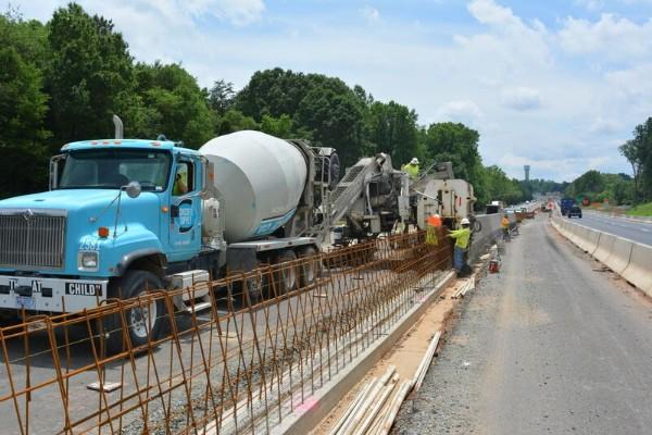 Workers build concrete barriers along I-77 north of Charlotte, as part of the I-77 Express Lanes project.