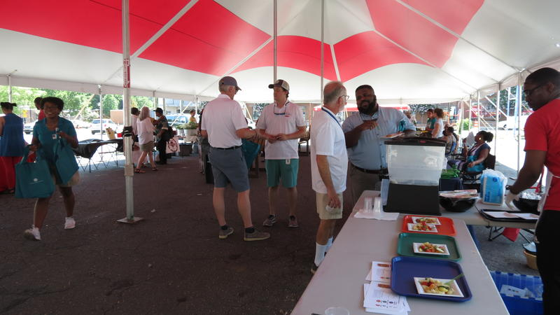 Diverse crowd and farmers gather under large tent at the expanded Rosa Parks Farmer's Market