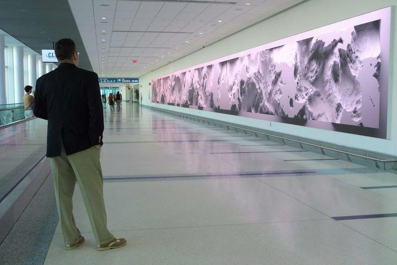Interconnected includes three large digital screens with constantly changing images derived from airport data.