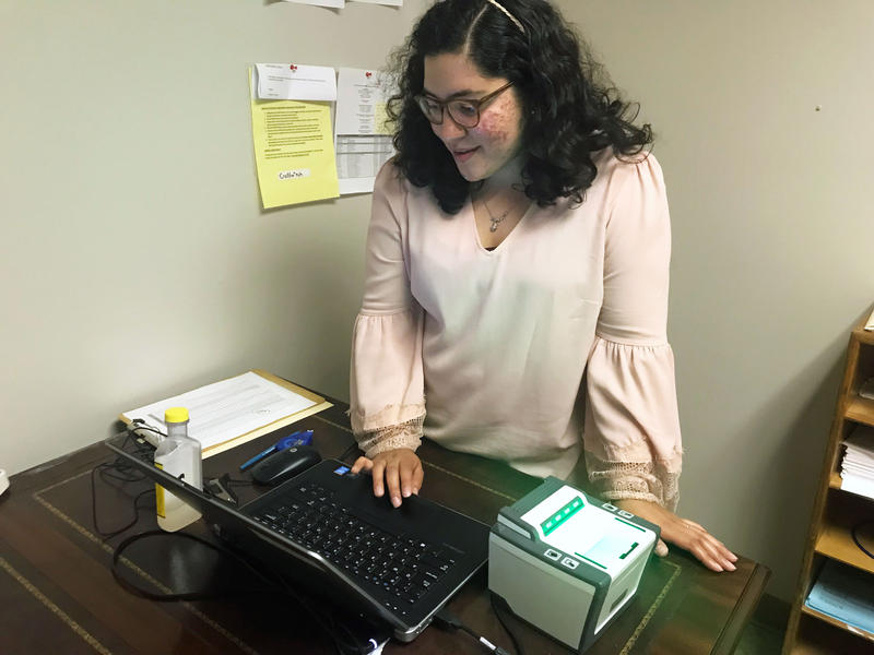 Stefania Arteaga scans fingerprints and conducts background checks for potential sponsors.