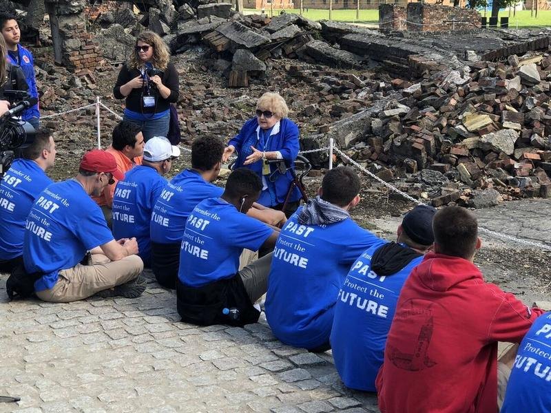 Holocaust survivor Eva Mozes Kor with Davidson players at site of Auschwitz concentration camp