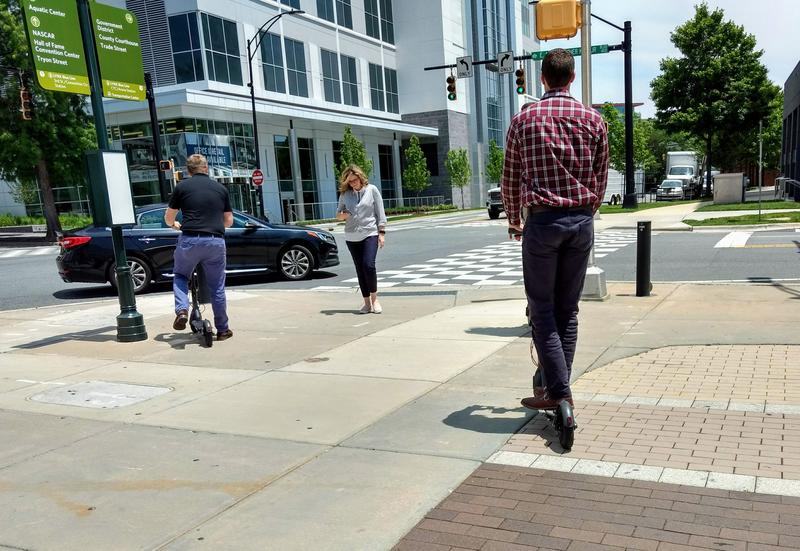 People rode scooters on a sidewalk in uptown Charlotte at lunch hour in June.