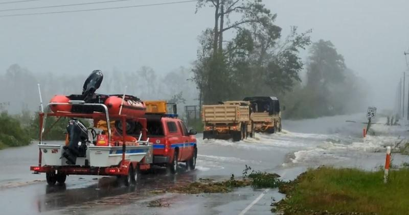 National Guard trucks lead an Illinois swift water rescue crew and other vehicles across a flooded section of US 74 Business near Whiteville Sunday.