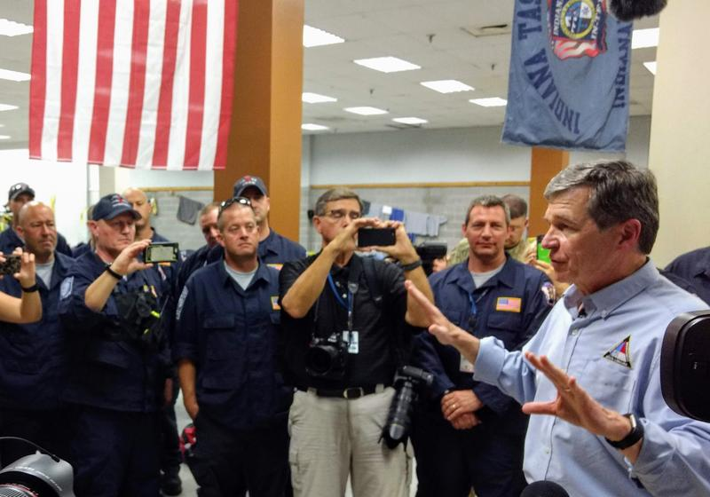Roy Cooper talks with out-of-state emergency workers at a temporary dormitory in Wilmington Tuesday.
