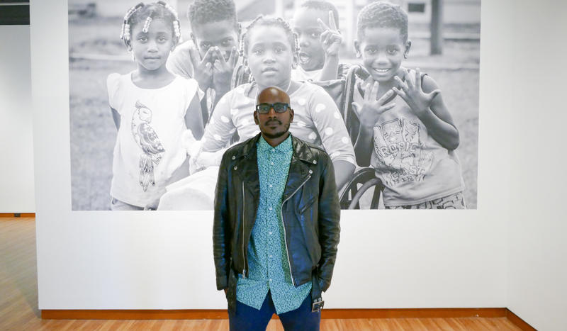 Alvin C. Jacobs stands in front of one of his pictures from his new exhibit on Brookhill Village.