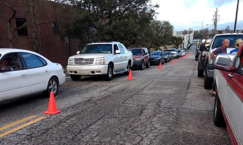 Cars lined up to get food and supplies at two distribution points in Wilmington Tuesday, Sept. 18.