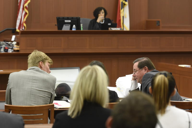 Kevin Olsen speaks to his attorney George Laughrun during trial in a Mecklenburg County courtroom on Tuesday