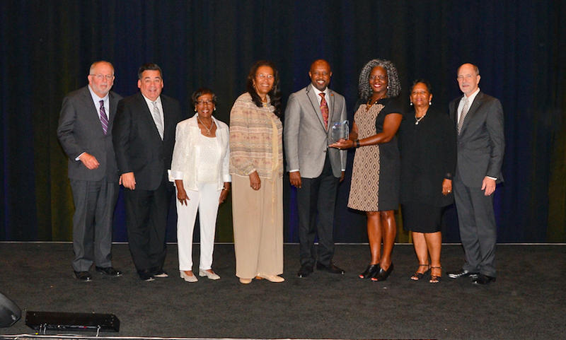 CMS officials and Superintendent Clayton Wilcox, second from left, accept the CUBE award.