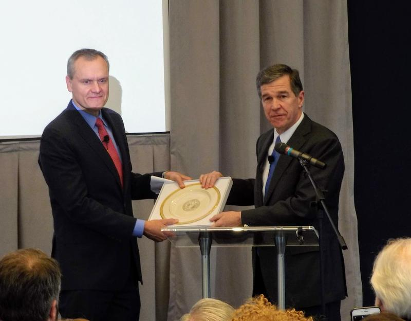 Gov. Roy Cooper (right) presents Honeywell CEO Darius Adamczyk with a plate holding the North Carolina state seal during Friday's announcement that Honeywell is moving its headquarters to Charlotte from New Jersey.