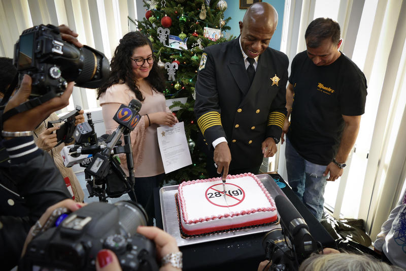 At a Wednesday press conference at Manolo's Bakery on Central Avenue, newly-elected Sheriff Garry McFaddan cut into a 287g cake alongside activist Stefania Areteaga and the bakery's owner.