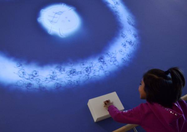 """A young girl plays with the new permanent interactive display at the Levine Children's Hospital. The work represents the mythological concept of """"The Heroes Journey"""", where a hesitiant hero confronts challenges, and is empowered in the process."""