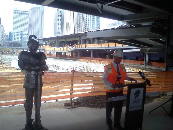 A knight's suit of armour stands watch over press conference in the under-construction baseball stadium.