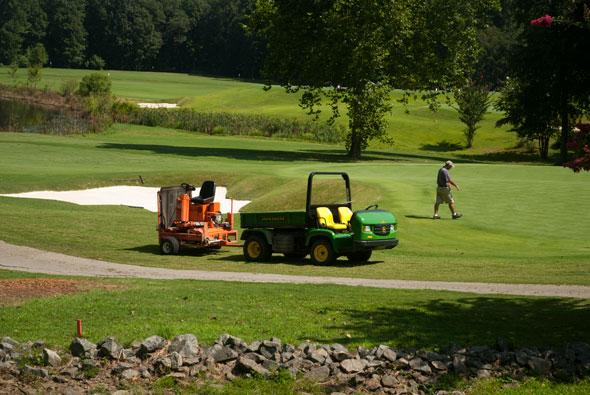 A groundskeeper worked on a green at River Run Country Club Monday.