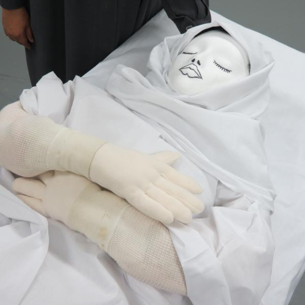 The hands of the dummy are crossed as they would be during prayer.