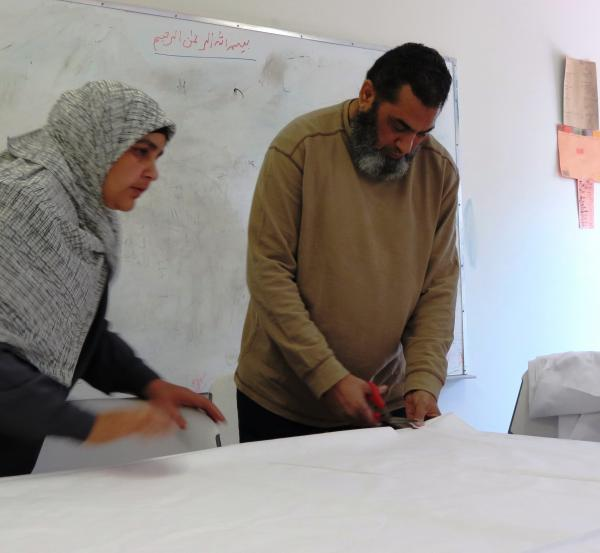 Zainab Ahmed instructs Yaseen Valam of the Cemetery Committee to cut yards of white cotton cloth into five pieces to shroud the female dummy. Muslim men only require three pieces of cloth, each 7 x 7 feet.