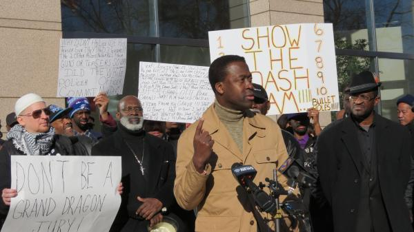 The Rev. Dwayne Collins speaks at the prayer vigil outside the Government Center on Monday morning.
