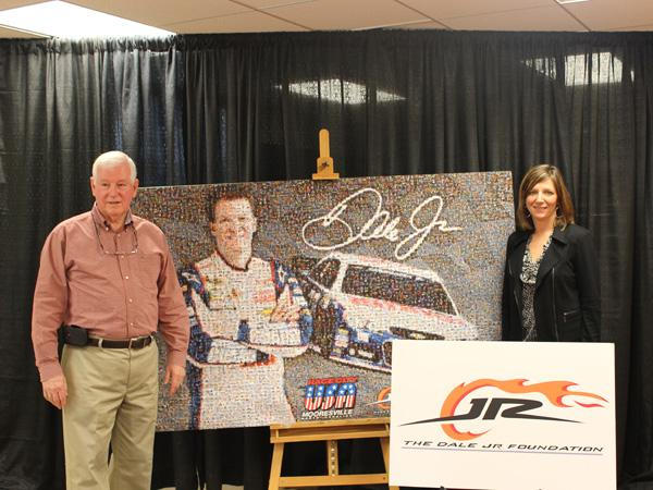 Leo Gordon, pictured left, treasurer of the Mooresville artist guild stands next to the four by six feet mural of Dale Earnhardt Jr. placed for auction.