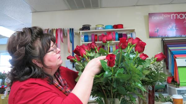 Mignon Long, a floral designer at Gallery of Flowers in Charlotte, counts to make sure there are 36 roses in the bouquet on a Valentine's Day order.