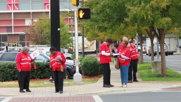 AARP volunteers examine and report the cracks in the sidewalk on the intersection of Charlottetowne and Metropolitan Avenue near uptown.