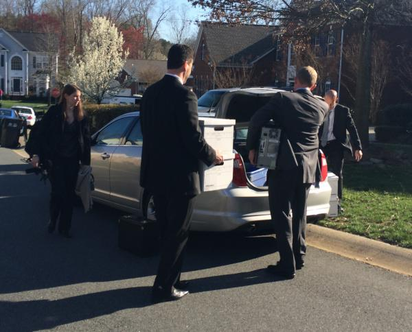 FBI agents load a CPU and boxes into cars outside Patrick Cannon's house and then drive off without saying a word.