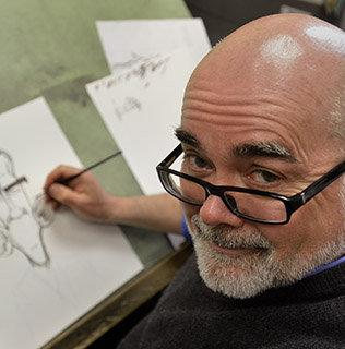 Charlotte Observer cartoonist Kevin Siers at the drawing board.