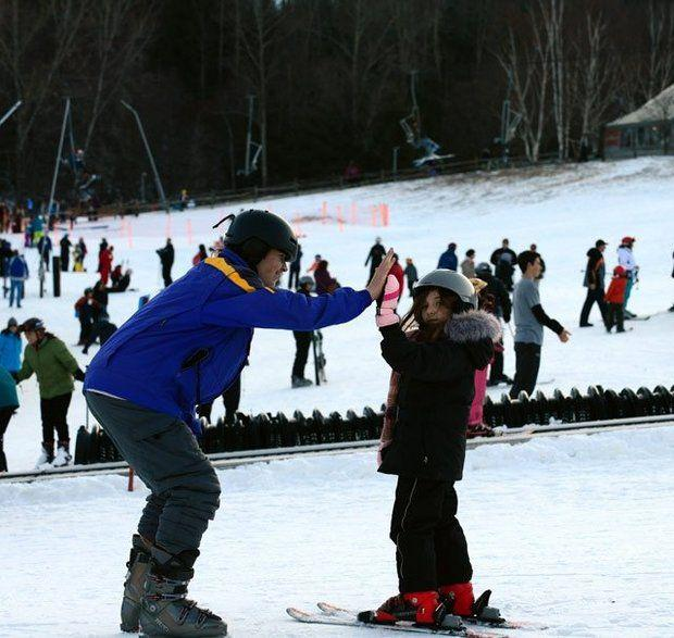 A child learning to ski gets encouragement from an instructor at Ski Butternut.