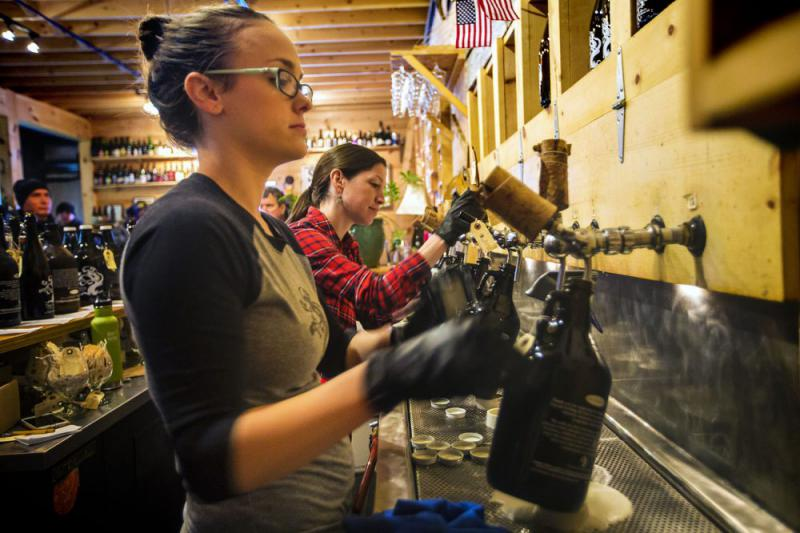 Employees at Tree House Brewing in Monson, Mass., fill beer growlers.