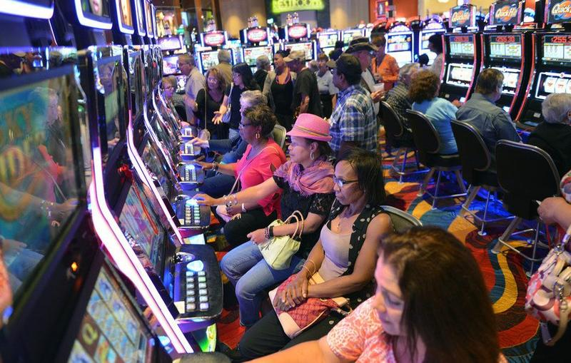 People playing the slot machines at the Plainridge Park Casino