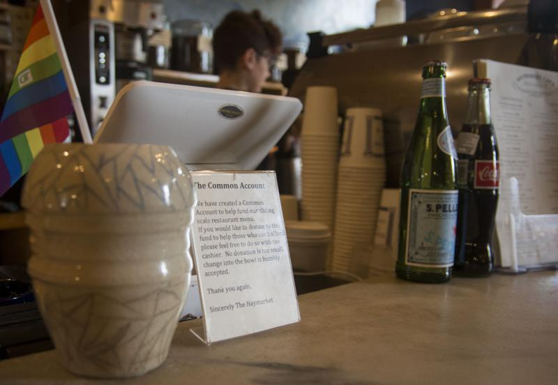 "A jar next to the register in the Haymarket Cafe in Northampton, Massachusetts collects money for a ""common account"" for diners who can't afford to pay for their meals."