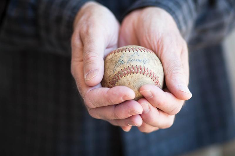 Robert Floyd, holding the ball signed by Jimmy Piersall.