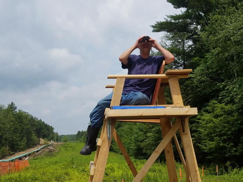 Sue Baxter owns land abutting where a New York-to-Connecticute pipeline is being constructed. She sits atop a lifeguard chair made for her by friends, as she keeps an eye on the project.