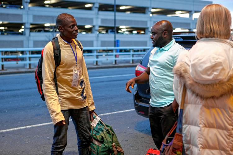Congolese refugee Guylain, 23, left, is greeted by his Catholic Charities caseworker Jowel Iranzi April 5, 2017 at Bradley International Airport in Windsor Locks, Conn., where Guylain and his brother Oliver, 26, arrived.