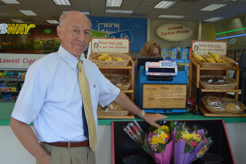 Bob Bulduc, owner of the Pride Station and Store chain, stands beside the machine that printed a $758.7 million jackpot.