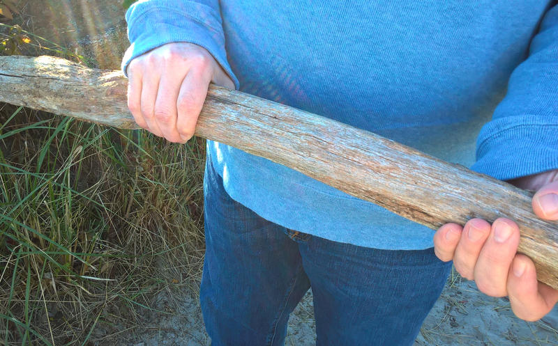 Steve Spofford holds a piece of wood he found that he believes is a remnant from the 1947 fires in Maine.
