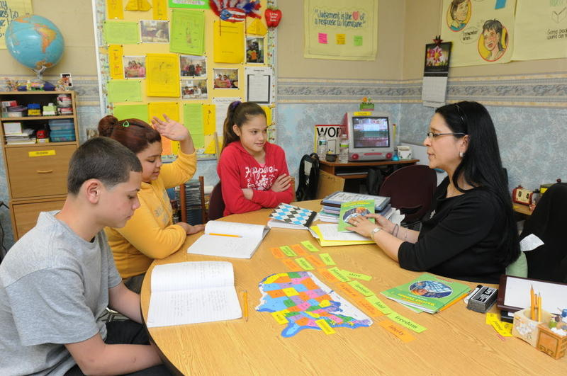 In a file photo, Elena Danek, right, an English language development teacher at Lt. Clayre P. Sullivan School in Holyoke, Massachusetts, teaches Anthony Hernandez, 13, Poala Viera, 12, and Natacha Hernandez, 12.