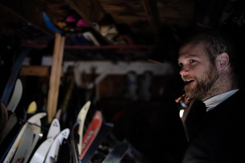 Rory Gawler stands in a storage room of a house he bought in a foreclosure sale. Without electricity, he uses a flashlight to illuminate the hundreds of skis he found inside.