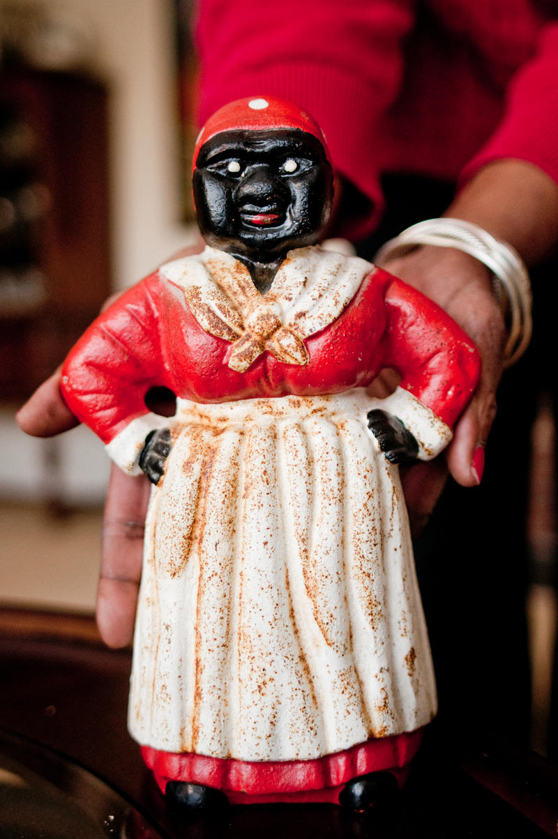 Dora Robinson holds the cast-iron figure of Aunt Jemima, originally used as a doorstop, which she found at a yard sale in upstate New York.