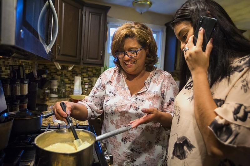 Irma Flores stirs milk while her daughter Gabriela Portillo-Perez speaks with her grandmother Isabel in El Salvador. The Trump administration announced Monday it would be ending temporary protected status for refugees from El Salvador.