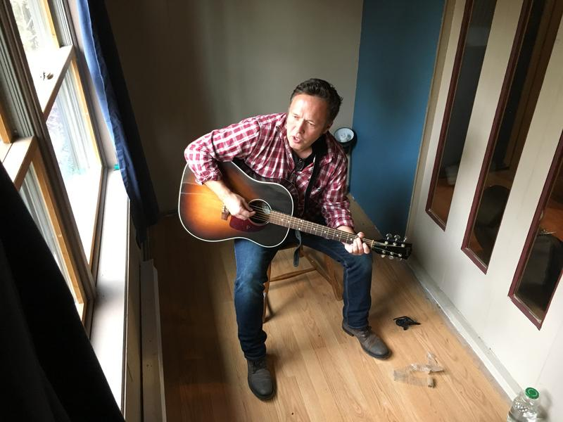 Singer songwriter Abe Loomis plays his guitar in a sound isolating recording booth in a studio in Conway, Massachusetts.