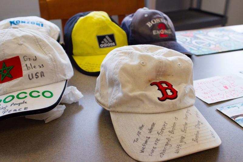 Hats and signs that were left at the pop-up memorial for the Boston Marathon bombing are arranged on tables at the Boston City Archives.