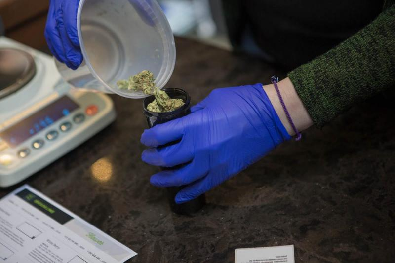 A sales associate at New England Treatment Access in Brookline, a medical dispensary, places medicinal marijuana into a container.