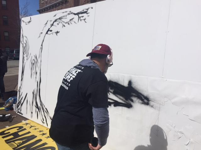 Manuel Oliver creates a mural outside South Congregational Church in Springfield, Massachusetts, on April 20, 2018.