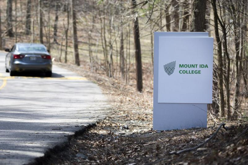 A car drives past the Mount Ida College sign on Carlson Avenue in Newton, Massachusetts.